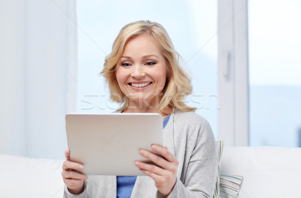 happy middle aged woman with tablet pc at home Stock photo © dolgachov