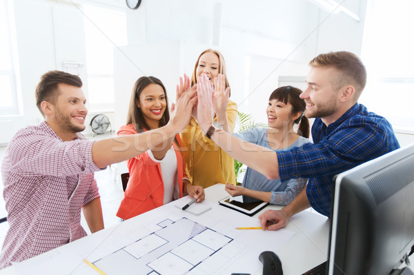 creative team making high five at office Stock photo © dolgachov