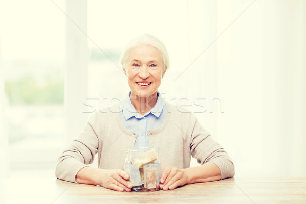 senior woman with money in glass jar at home Stock photo © dolgachov