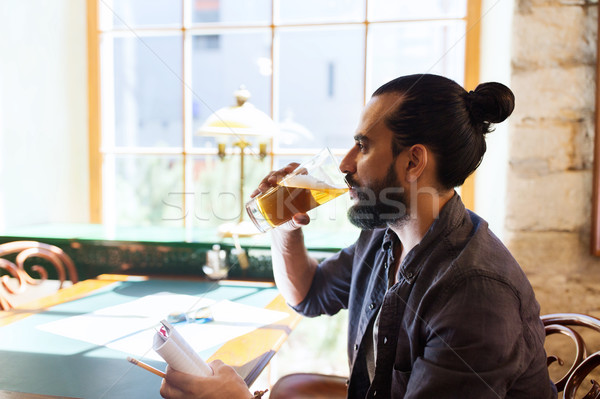 man with notebook drinking beer at bar or pub Stock photo © dolgachov