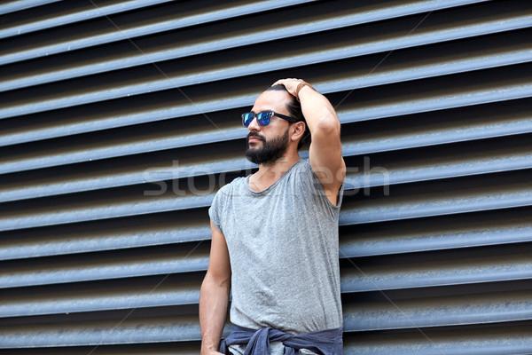 man with beard and sunglasses on city street Stock photo © dolgachov