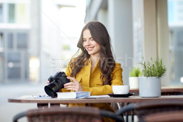 happy tourist woman with camera at city cafe Stock photo © dolgachov