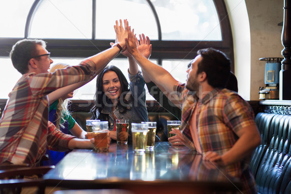 happy friends with beer making high five at pub Stock photo © dolgachov