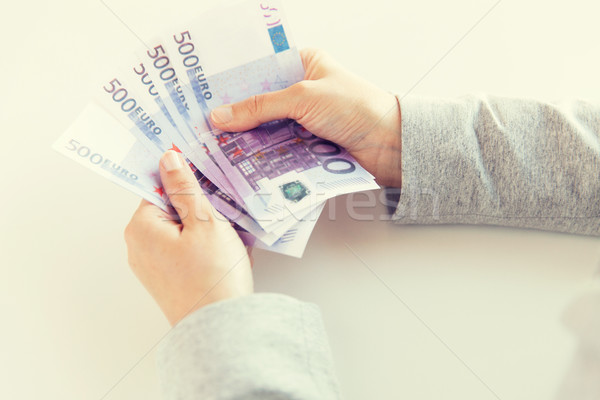 Stock photo: close up of woman hands counting euro money