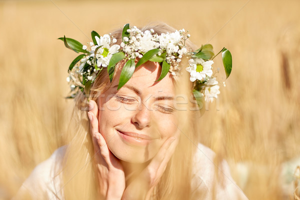 happy woman in wreath of flowers on cereal field Stock photo © dolgachov