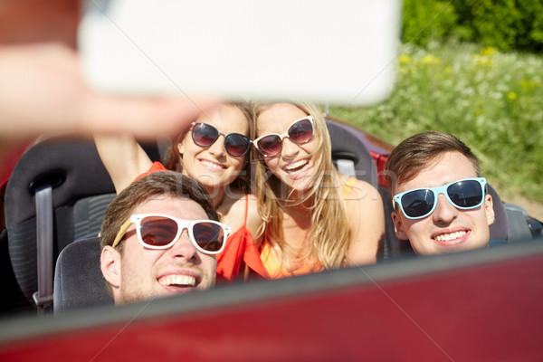 Stock photo: friends driving in cabriolet car and taking selfie