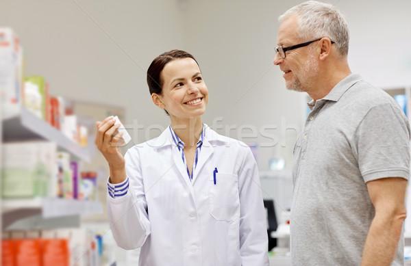 Gyógyszerész mutat drog idős férfi gyógyszertár Stock fotó © dolgachov