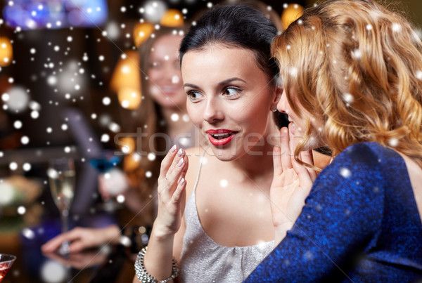 happy women gossiping at night club over snow Stock photo © dolgachov