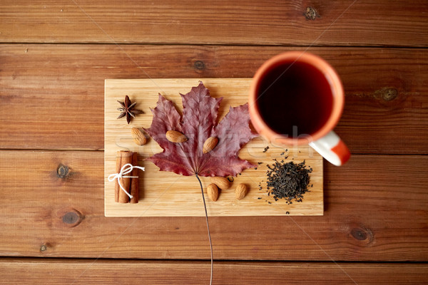 cup of tea, maple leaf and almond on wooden board Stock photo © dolgachov