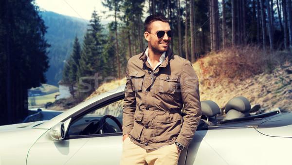 happy man near cabriolet car over nature Stock photo © dolgachov