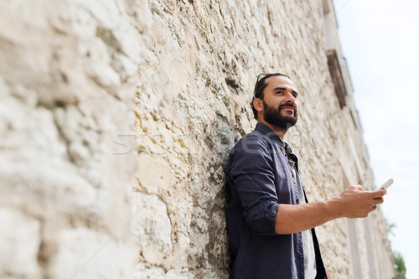 man with smartphone at stone wall Stock photo © dolgachov