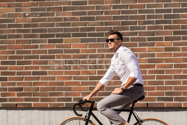 young man riding bicycle on city street Stock photo © dolgachov