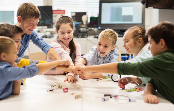 happy children making fist bump at robotics school Stock photo © dolgachov