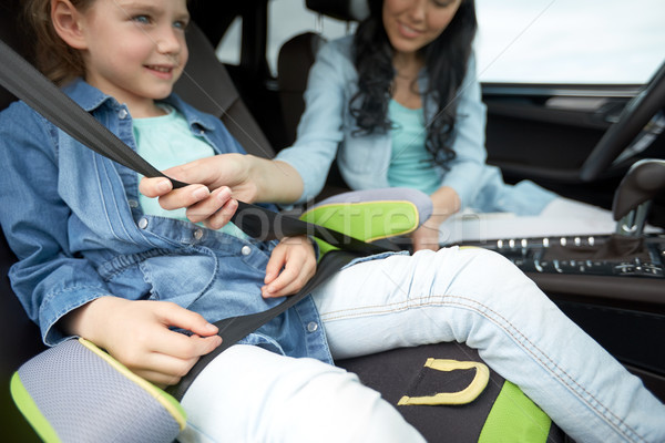 woman fastening child with safety seat belt in car Stock photo © dolgachov