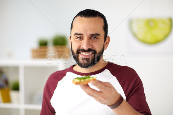 man eating avocado sandwiches at home kitchen Stock photo © dolgachov