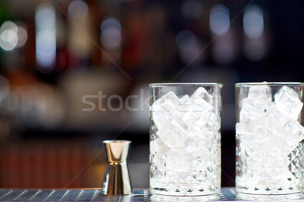 glasses with ice and jigger on bar counter Stock photo © dolgachov