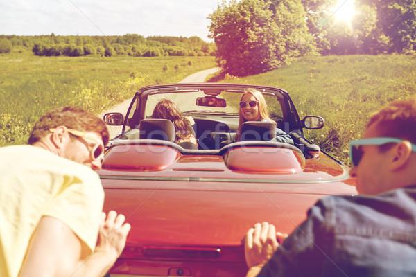 Felice amici spingendo rotto cabriolet auto Foto d'archivio © dolgachov