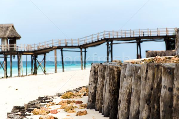 stilt bridge to bungalow hut on tropical beach Stock photo © dolgachov