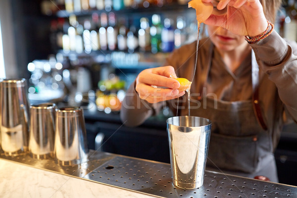 bartender with shaker preparing cocktail at bar Stock photo © dolgachov