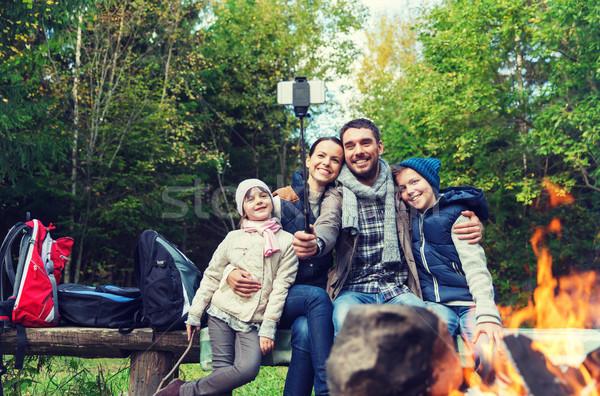 family with smartphone taking selfie near campfire Stock photo © dolgachov