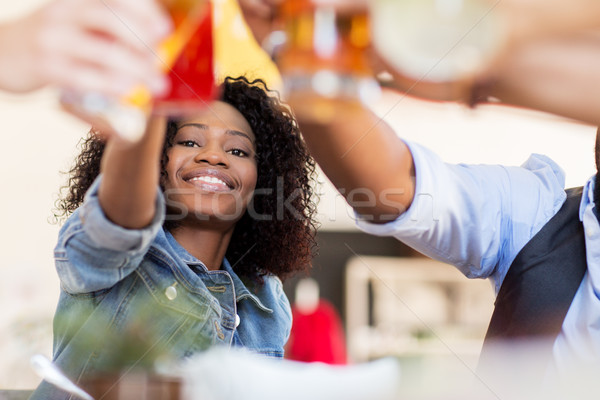 friends clinking glasses with drinks at restaurant Stock photo © dolgachov