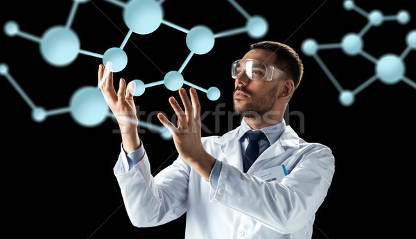 scientist in lab coat and goggles with molecules Stock photo © dolgachov