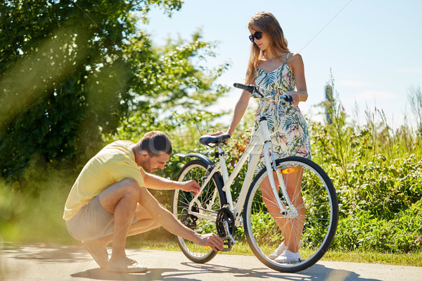 young couple fixing bicycle on country road Stock photo © dolgachov