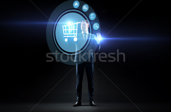 Stock photo: businessman with shopping cart on virtual screen