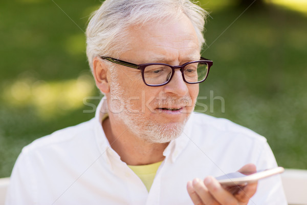 old man using voice command recorder on smartphone Stock photo © dolgachov