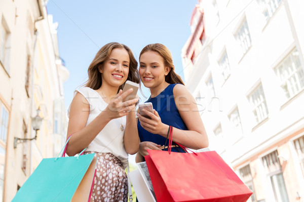 happy women with shopping bags and smartphones Stock photo © dolgachov