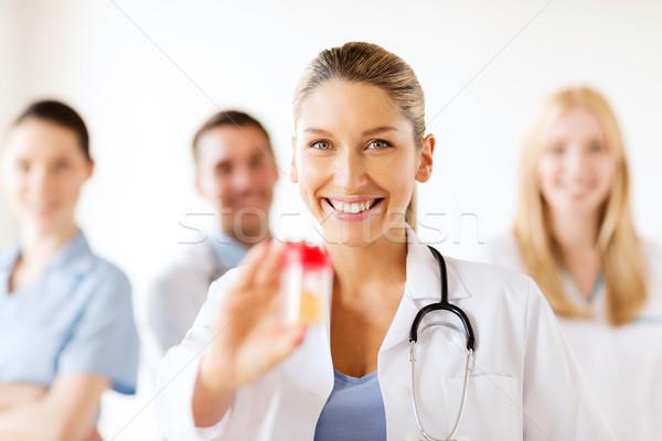 female doctor with jar of capsules Stock photo © dolgachov