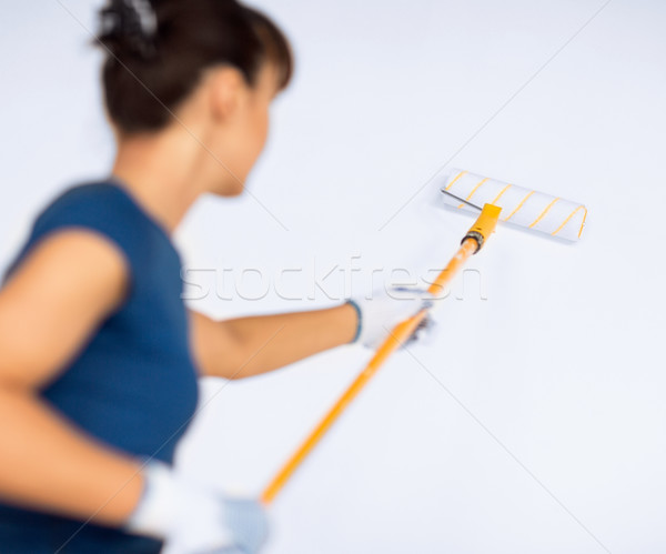 woman with roller and paint colouring the wall Stock photo © dolgachov