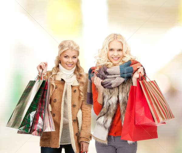 women in winter clothes with shopping bags Stock photo © dolgachov
