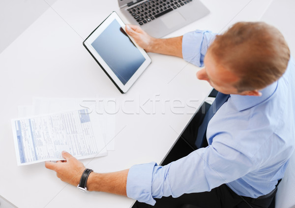 Stock photo: businessman with tablet pc and papers in office