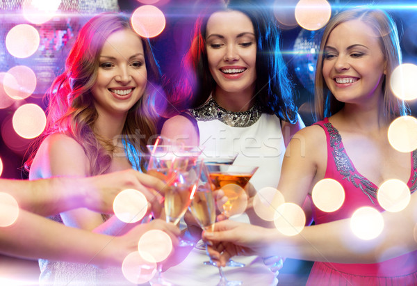 three smiling women with cocktails in club Stock photo © dolgachov