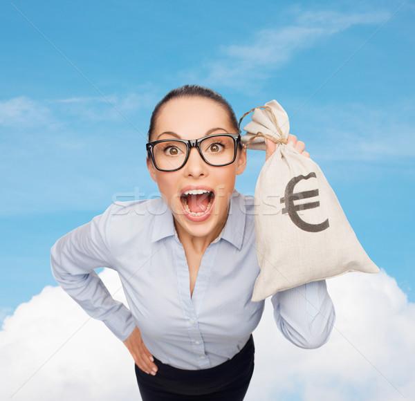 amazed businesswoman holding money bag with euro Stock photo © dolgachov