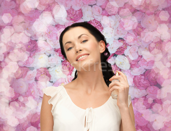 beautiful woman spraying pefrume on her neck Stock photo © dolgachov