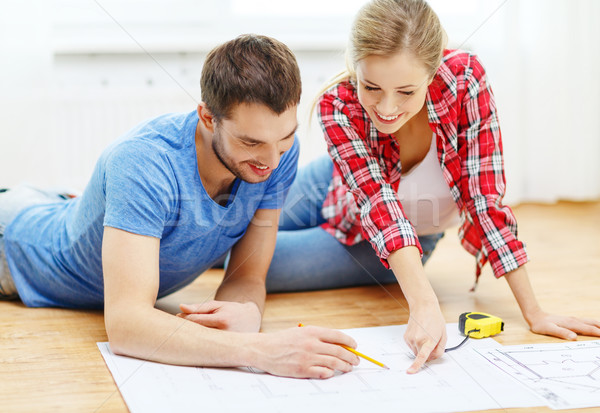 smiling couple looking at blueprint at home Stock photo © dolgachov