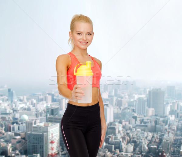 Glimlachend vrouw eiwit schudden fles Stockfoto © dolgachov