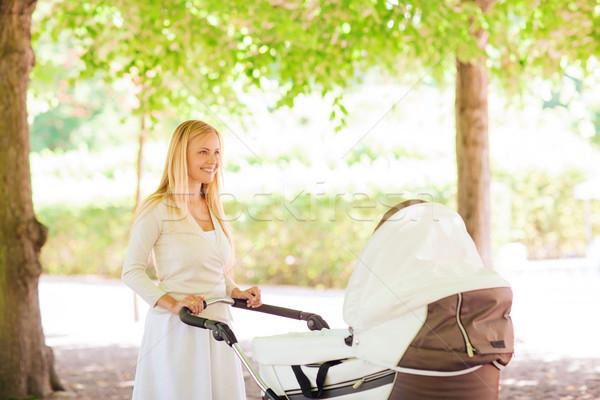 happy mother with stroller in park Stock photo © dolgachov