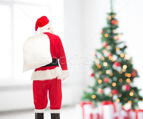 man in costume of santa claus with bag Stock photo © dolgachov