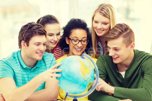 five smiling student looking at globe at school Stock photo © dolgachov