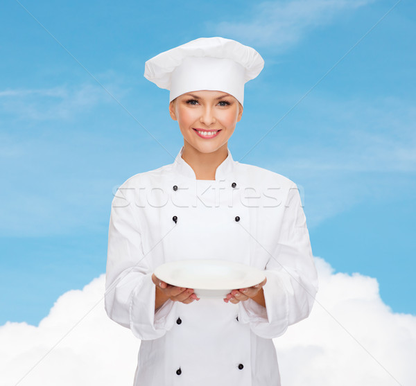 smiling female chef with empty plate Stock photo © dolgachov