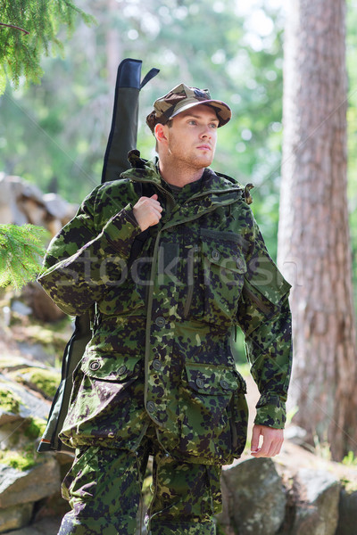 young soldier or hunter with gun in forest Stock photo © dolgachov