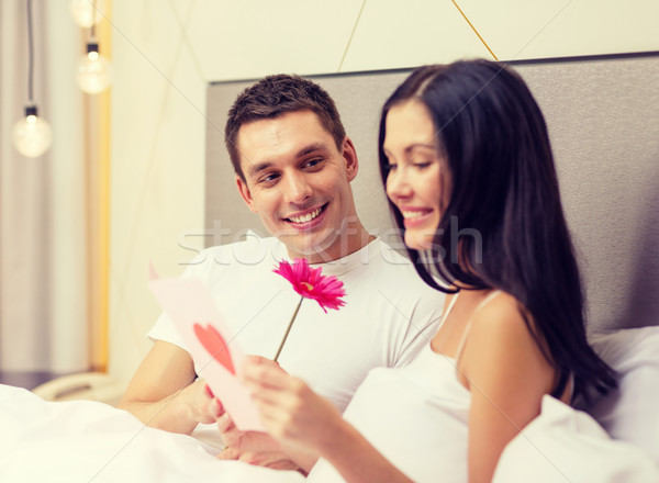 Uśmiechnięty para bed pocztówkę kwiat hotel Zdjęcia stock © dolgachov