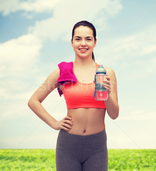 sporty woman with towel and water bottle Stock photo © dolgachov