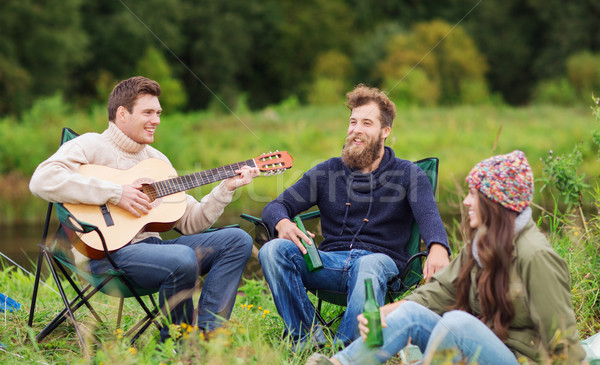 group of tourists playing guitar in camping Stock photo © dolgachov