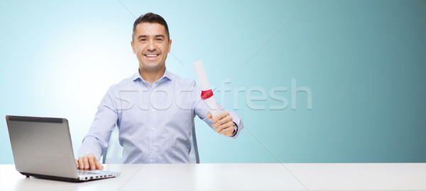 smiling man with diploma and laptop at table Stock photo © dolgachov