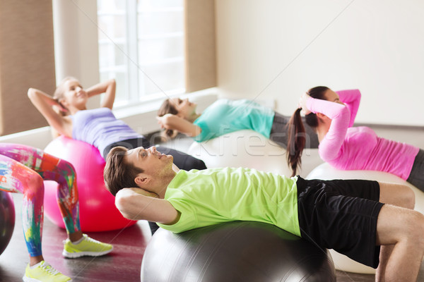happy people flexing abdominal muscles on fitball Stock photo © dolgachov