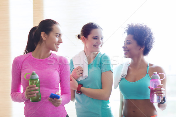Stock photo: happy women with bottles of water in gym